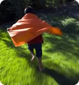 Young boy running with his cape billowing behind